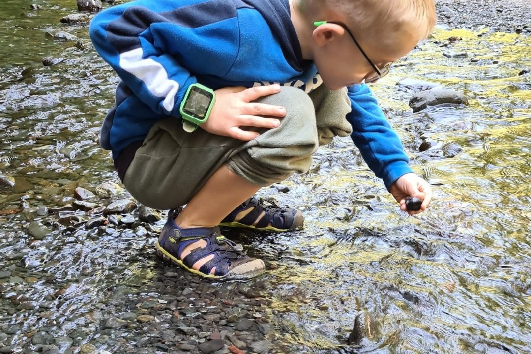 child in a stream wearing a pair of waterproof hiking sandals