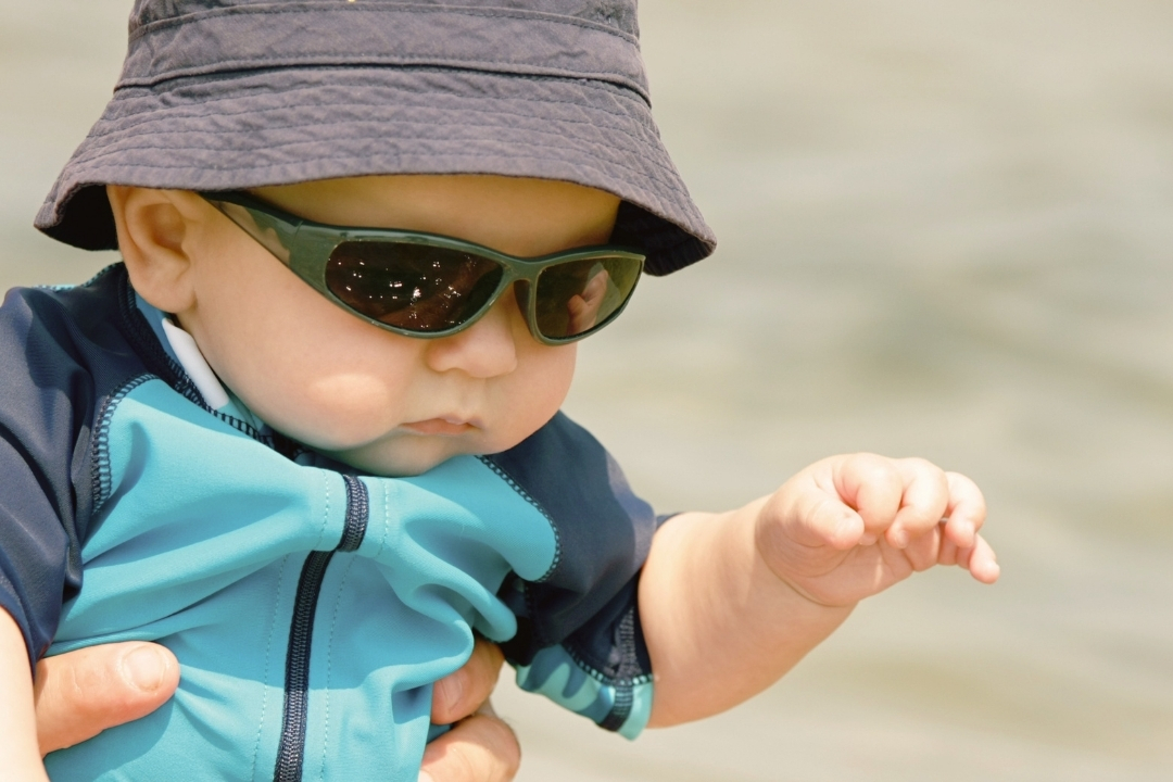 small baby boy in a blue rashguard with sun hat and sunglasses