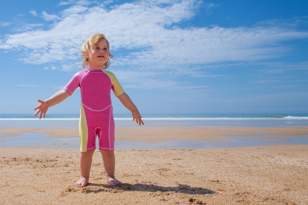 a small child in a pink baby rash guard