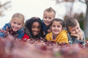 Kids playing outside in the leaves